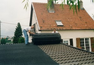 Die am Boden montierte und aufgerollte Poolheizung wird auf dem Dach ausgerollt.